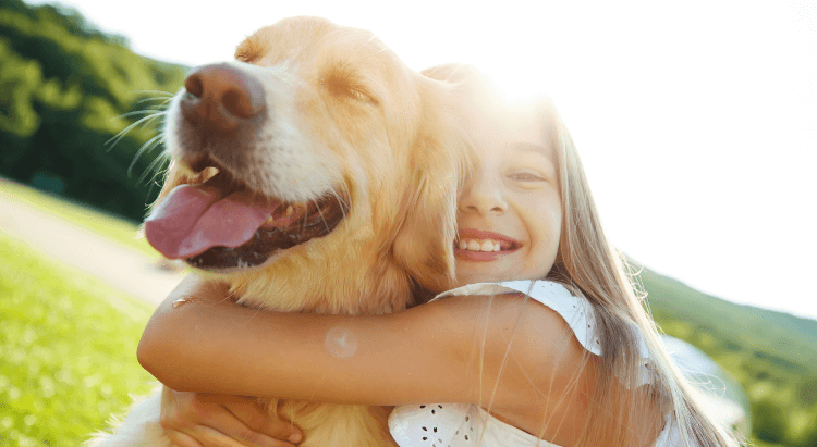 A young girl holding a dog